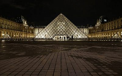 People stand outside the Louvre Pyramid of the Louvre museum at night on February 3, 2017, in Paris, after a French soldier patrolling at the Louvre shot and seriously injured a machete-wielding attacker earlier. (AFP PHOTO / GEOFFROY VAN DER HASSELT)