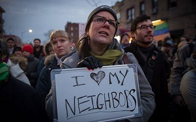 A woman holds a sign as the Astoria community stands together with Muslim-Americans and Muslim immigrants at a rally, February 3, 2017 in New York. (AFP PHOTO / Bryan R. Smith)