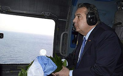 Greek Defense Minister Panos Kammenos prepares to throw a wreath over the area of the Imia Islets in the Aegean Sea from a helicopter on February 2, 2017 in memory of three Greek Air Force officers who lost their lives during a crisis between Greece and Turkey back in 1996. (Stringer/Eurokinissi/AFP)