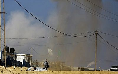A Palestinian man runs for cover as smoke rises following an Israeli airstrike on a Hamas post in the northern Gaza Strip, February 6, 2017. (AFP/Mohammed Abed)