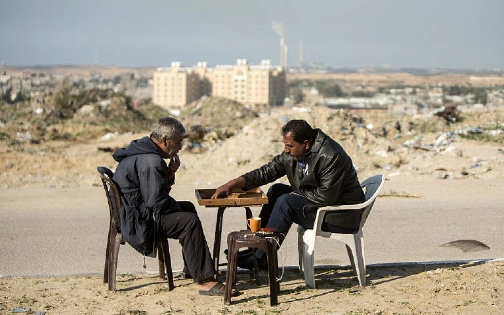 Palestinian men play backgammon next their home in northern Gaza on February 6, 2017, amid a wave of IDF airstrikes on Hamas positions after a rocket was fired at Ashkelon from the Strip (AFP PHOTO/MAHMUD HAMS)