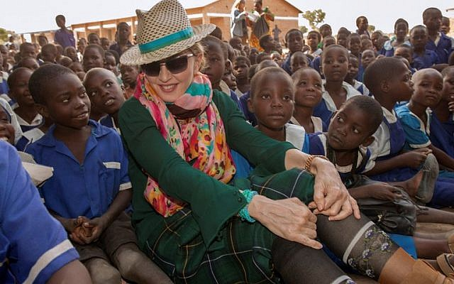 This file photo taken on November 30, 2014 shows US popstar Madonna sitting among Malawian children in the Kasungu District, Central Malawi. (AFP/Amos Gumulira)