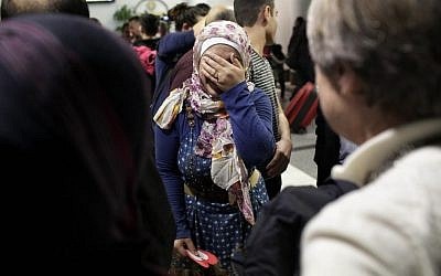 After she and her family were previously banned from entering the United States due to an executive order signed by US President Donald Trump, Syrian refugee Baraa Haj Khalaf, center covers her face as she reacts  to greetings from people during her arrival at O'Hare International Airport, in Chicago, Illinois, February 7, 2017. (AFP/Joshua LOTT)