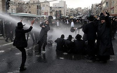 Police use water cannons on ultra-Orthodox men protesting IDF conscription in Jerusalem, on February 9, 2017. (AFP Photo/Ahmad Gharabli)
