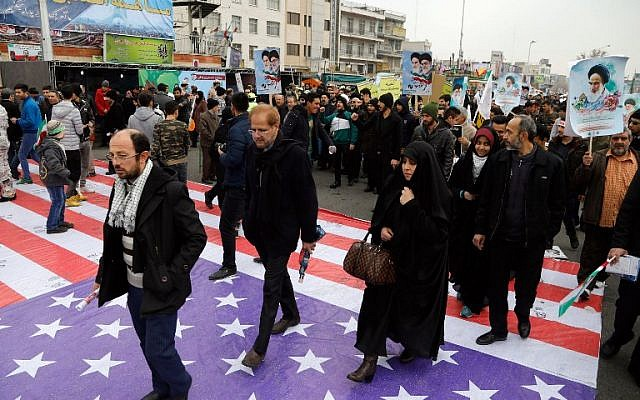 "Iranians step on a giant US flag as they take part in a rally marking the anniversary of the 1979 Islamic revolution on February 10, 2017, in the capital Tehran. Millions of Iranians marched on the anniversary day in what President Hassan Rouhani described as a response to the new US administration and a rejection of ""threatening language"". (Atta Kenare/AFP)"