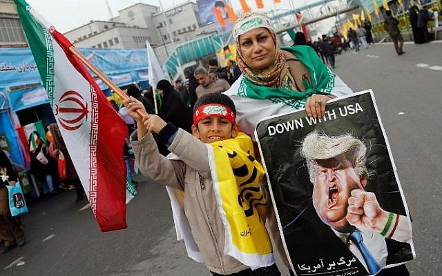 An Iranian woman holds a placard showing a caricature of US President Donald Trump being punched by a hand wearing a bracelet of the Iranian flag during a rally marking the anniversary of the 1979 Islamic revolution on February 10, 2017, in the capital Tehran. (Atta Kenare/AFP)