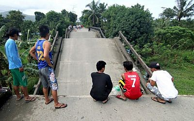 Residents stand on one end of a bridge, linking the city of Surigao to nearby towns, which was damaged after a 6.5-magnitude earthquake struck overnight, in Surigao City in southern island of Mindanao in the Philippines on February 11, 2017. (AFP/Erwin Mascarinas)