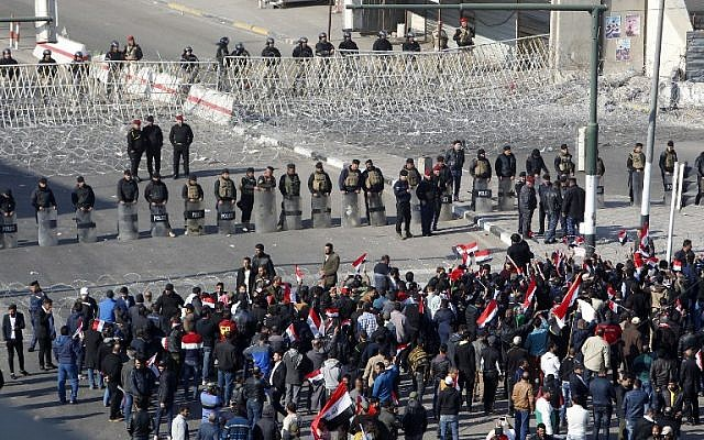 Iraqi security forces stand guard as supporters of the Sadrist movement gather during a demonstration in Baghdad's Tahrir Square on February 11, 2017, to demand the formation of an independent electoral commission. (AFP PHOTO/SABAH ARAR)
