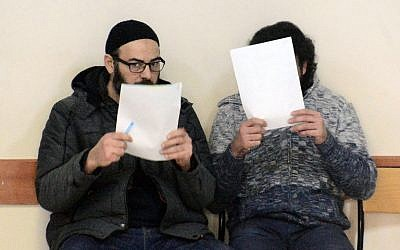 Alleged Islamic State members Abdullah El Halabi (L) and Mohammed Tofik Saleh wait at the Adana police station after being detained by Turkish police in Adana on February 11, 2017. (AFP/Dogan News Agency/Stringer)