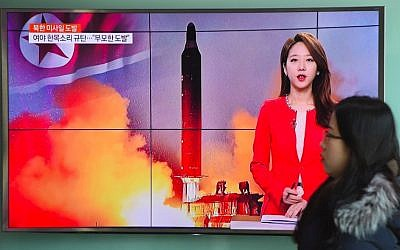 A woman walks past a television screen showing file footage of North Korea's missile launch at a railway station in Seoul, South Korea, February 12, 2017. (AFP/Jung Yeon-Je)