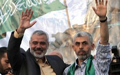 Then-Hamas leader Ismail Haniyeh (L) and freed Palestinian security prisoner Yahya Sinwar, a founder of the terror group's military wing, wave as supporters celebrate the release of hundreds of inmates in a swap for captured IDF soldier Gilad Shalit, in Khan Yunis, southern Gaza on October 21, 2011. (AFP/Said Khatib)
