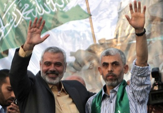 Then-Hamas leader Ismail Haniyeh (L) and freed Palestinian prisoner Yahya Sinwar, a founder of the terror group's military wing, wave as supporters celebrate the release of hundreds of inmates in a swap for captured IDF soldier Gilad Shalit, in Khan Yunis, southern Gaza on October 21, 2011. (AFP/Said Khatib)
