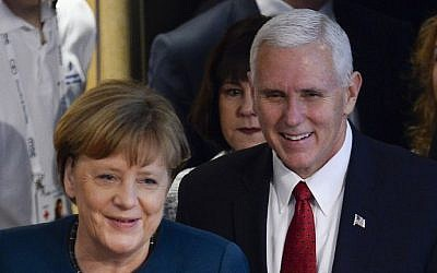 German Chancellor Angela Merkel (L) and US Vice President Mike Pence arrive at the 2nd day of the  53rd Munich Security Conference (MSC) at the Bayerischer Hof hotel in Munich, southern Germany, on February 18, 2017. (AFP PHOTO / THOMAS KIENZLE)