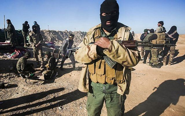 A masked fighter of the Hashed al-Shaabi (Popular Mobilization) paramilitaries poses for a picture carrying a Kalashnikov assault rifle by defensive positions on the outskirts of Tal Afar west of Mosul, where Iraqi forces are preparing for the offensive retake the western side of Mosul from Islamic State (IS) group fighters, on February 18, 2017. ( AFP PHOTO / AHMAD AL-RUBAYE)