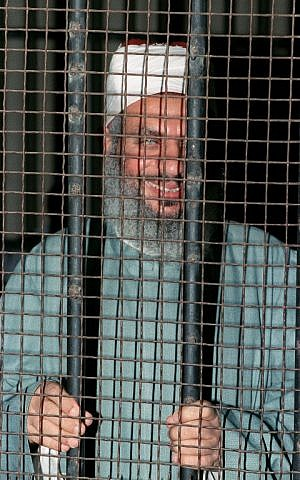 Sheikh Omar Abdel Rahman smiles inside an iron cage at the opening of a court session in Cairo on August 6, 1989. (AFP PHOTO/MIKE NELSON)