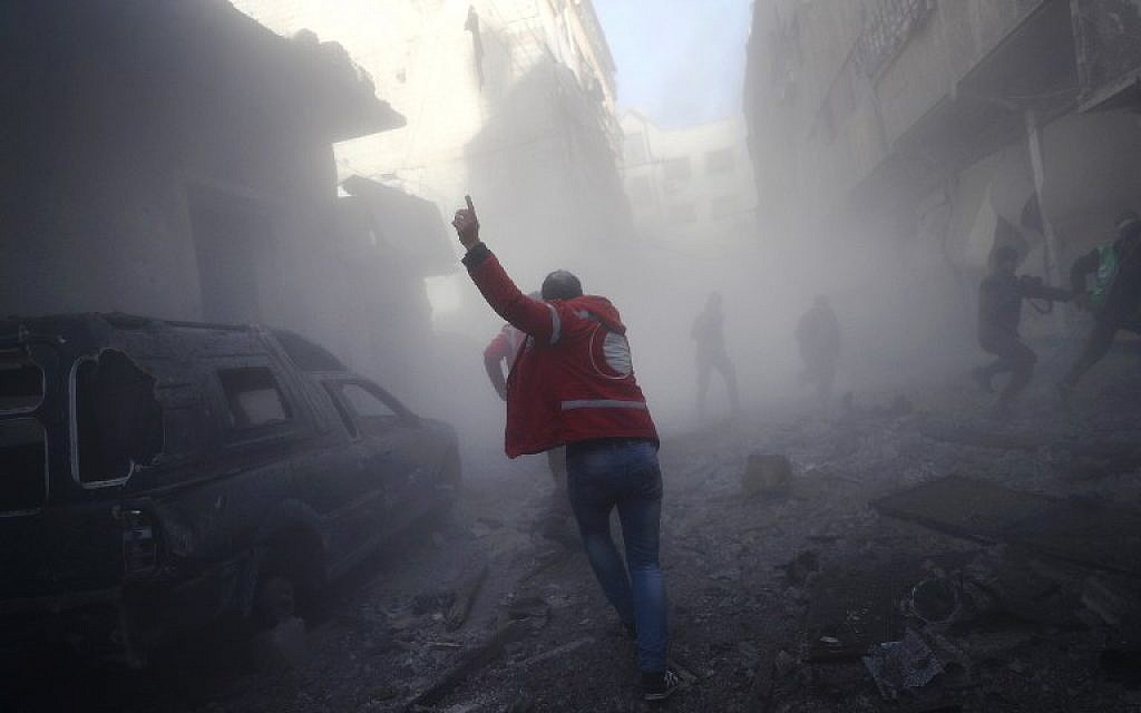 A member of the Syrian Arab Red Crescent runs as he searches for victims following a reported government airstrike on the rebel-held town of Douma, on the eastern outskirts of the capital Damascus, on February 19, 2017. (AFP /Abd Doumany)
