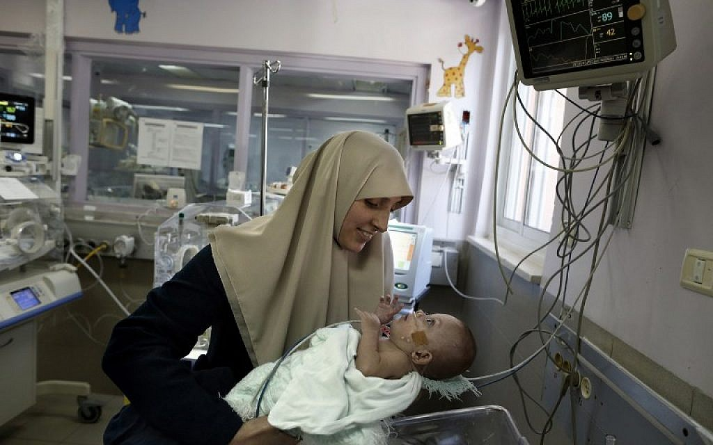Gazan Jumana Daoud carries her 7-month-old daughter Maryam at Makassed Hospital in East Jerusalem on February 20, 2017, as they meet for the first time since the baby's premature birth. (AFP/AHMAD GHARABLI)