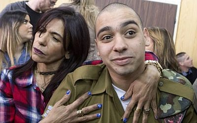 IDF soldier Elor Azaria, right, convicted on the manslaughter of a wounded Palestinian, is embraced by his mother Oshra at the start of his sentencing hearing in a military court in Tel Aviv, February 21, 2017. (AFP/POOL/ JIM HOLLANDER)
