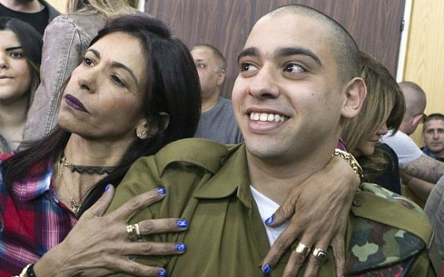 IDF soldier Elor Azaria, right, convicted on the manslaughter of a wounded Palestinian, is embraced by his mother Oshra at the start of his sentencing hearing in a military court in Tel Aviv, February 21, 2017. (AFP/Pool/Jim Hollander)