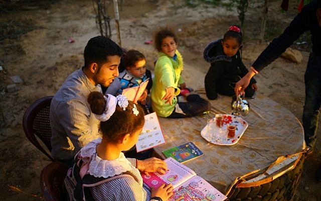 """Mossab Abo Toha, who is collecting english books for his """"Library and Bookshop for Gaza"""" project, reads english books with children in the garden at his family home in Beit Lahia in northern Gaza on February 20, 2017. (AFP Photo/Mohammed Abed)"""