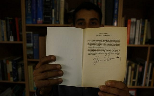 Mossab Abo Toha shows the signature of American philosopher Noam Chomsky, who personally dedicated some books to him, in the library at his family home in Beit Lahia in northern Gaza on February 20, 2017. (AFP Photo/Mohammed Abed)