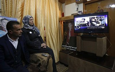 The father and mother of Palestinian attacker Abdul Fatah al-Sharif, who was shot dead as he lay on the ground by IDF soldier Elor Azaria, watch on television the verdict of the trial of the soldier, at their family home in the West Bank city of Hebron, February 21, 2017. (AFP/HAZEM BADER)