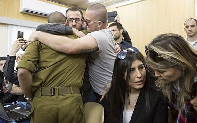 Israeli soldier Elor Azaria, who shot dead a wounded Palestinian assailant in March 2016, is embraced by family and friends at the start of his sentencing hearing in a military court in Tel Aviv on February 21, 2017. (AFP/ POOL / JIM HOLLANDER)