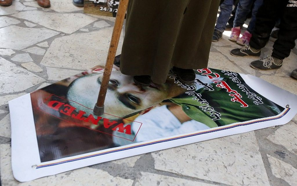 A Palestinian woman steps during a demonstration on a portrait of Israeli soldier Elor Azaria, on February 21, 2017 (AFP PHOTO / HAZEM BADER)