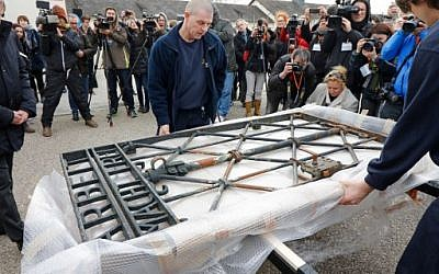 Workers unpack the original iron gate with the slogan 'Arbeit macht frei' ('Work will set you free') over the grounds of the former Nazi concentration camp in Dachau, southern Germany, February 22, 2017. (AFP Photo/Uwe Lein)