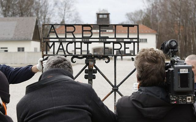 Journalists take pictures of the original iron gate with the slogan 'Arbeit macht frei' ('Work will set you free') at the former Nazi concentration camp in Dachau, southern Germany, on February 22, 2017. (AFP Photo/Uwe Lein)