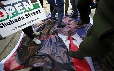Palestinian demonstrators stand on a poster of US President Donald Trump as they protest against his support of Israel and demand for the Israeli army to re-open Shuhada Street near a Jewish settler enclave in the heart of the flashpoint West Bank city of Hebron, which it has largely closed off to Palestinians, on February 24, 2017. (AFP/Hazem Bader)