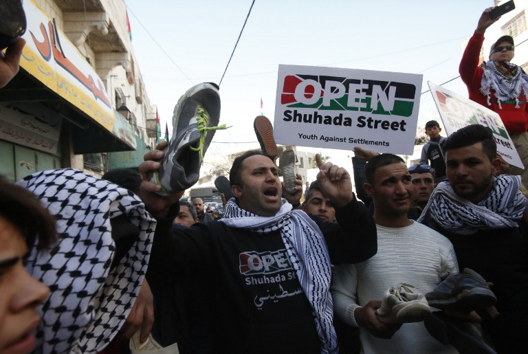 Palestinian demonstrators chant slogans during a protest demanding for the Israeli army to re-open Shuhada Street near a Jewish settler enclave in the heart of the flash point West Bank city of Hebron, which it has largely closed off to Palestinians on February 24, 2017. (AFP PHOTO / HAZEM BADER)
