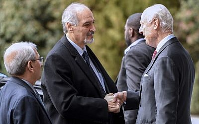Syrian UN Ambassador Bashar Jaafari (L) shakes hand with UN Syria envoy Staffan de Mistura (R) upon his arrival to take part in the second day of a new round of Syria peace talks, on February 24, 2017 in Geneva. (AFP Photo/Philippe Desmazes)