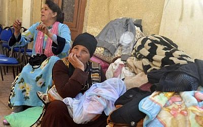 Egyptian Coptic Christians sit in the courtyard of the Evangelical Church in the Suez Canal city of Ismailiya on February 24, 2017, upon arriving to take refuge from Islamic State (IS) group jihadists. (Striner/AFP)