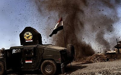 An explosion hits near a vehicle belonging to Iraq's elite Rapid Response Division during the assault to retake the northern city of Mosul, as Iraqi forces continue the offensive to retake the city's western half from IS, on February 25, 2017. (AFP/Aris Messinis)