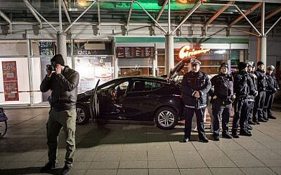 Police officers stand around a car in front of a business building in Heidelberg, western Germany, where a man ploughed into pedestrians before beeing shot by the police on February 25, 2017. (AFP PHOTO / Thomas Lohnes)