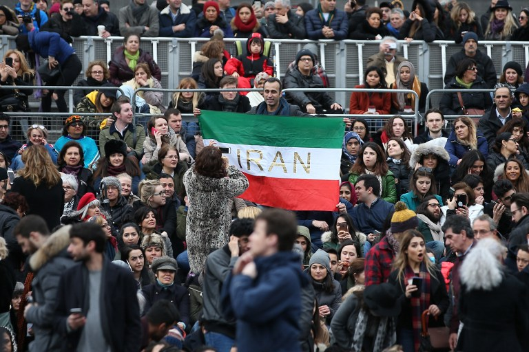 A man holds up an Iranian flag as people gather in Trafalgar Square for the public screening for the film 'The Salesman' in central London on February 26, 2017. (AFP PHOTO / Daniel LEAL-OLIVAS)