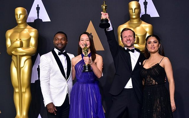 (L-R) Actor David Oyelowo, producer Joanna Natasegara and director Orlando von Einsiedel, winners of Best Documentary Short Subject for 'The White Helmets' and actress Salma Hayek pose in the press room during the 89th Oscars on February 26, 2017 in Hollywood, California. (AFP PHOTO / FREDERIC J. BROWN)