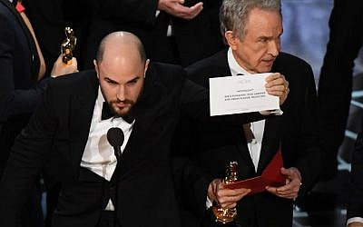 """La La Land"" producer Jordan Horowitz (L) shows the card reading Best Film 'Moonlight"" next to US actor Warren Beatty after the latter mistakingly read ""La La Land"" initially at the 89th Oscars on February 26, 2017 in Hollywood, California. (AFP PHOTO / Mark RALSTON)"