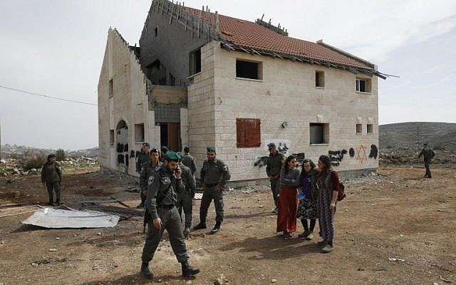 Israeli border guards and youths gather on February 27, 2017 outside a house slated for demolition in the Ofra settlement in the West Bank. (AFP/MENAHEM KAHANA)