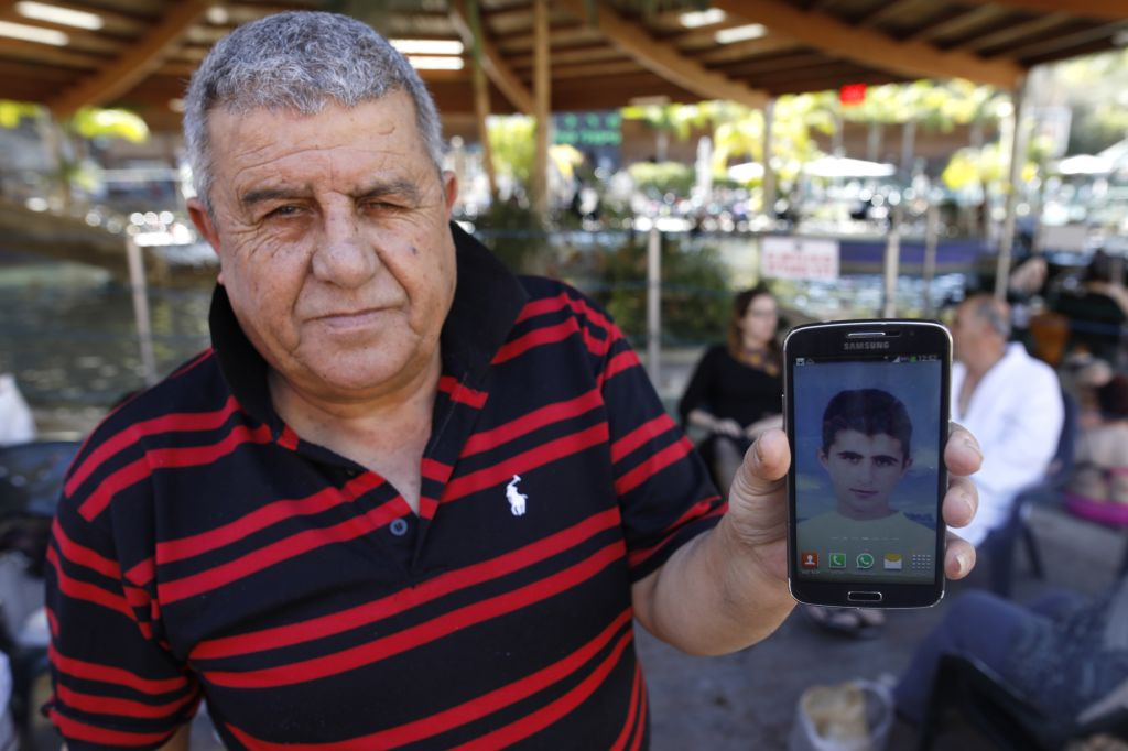 After bathing in the hot springs of Hamat Gader, Israel on February 20, 2017, Hamudi Ali, 67, shows a picture of his son Ahmad, who was killed in Gaza in 2003. (Courtesy)