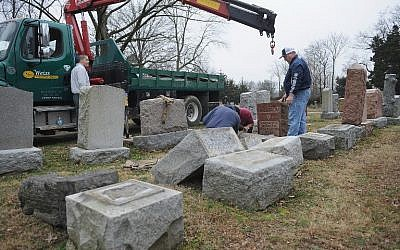 Volunteers from a local monument company help to reset vandalized headstones at Chesed Shel Emeth Cemetery on February 22, 2017 in University City, Missouri. (Michael Thomas/ Getty Images)