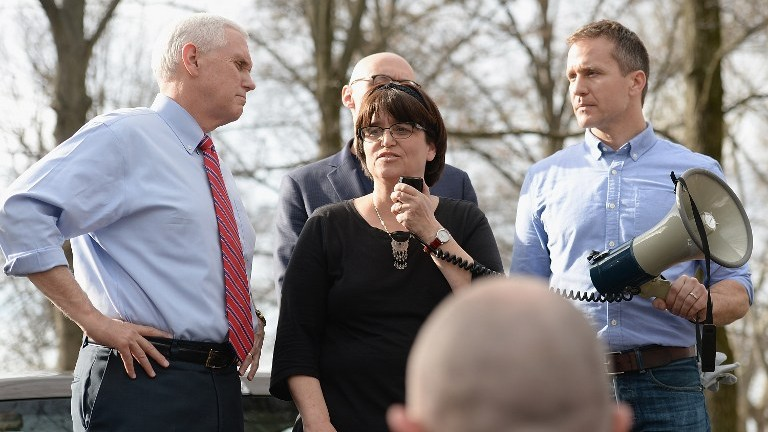 Anita Feigenbaum, executive director at Chesed Shel Emeth Cemetery speaks to the crowd on February 22, 2017 in University City, Missouri. Governor Eric Greitens (R) and US Vice President Mike Pence (L) were on hand to speak to over 300 volunteers who helped cleanup after the recent vandalism. (Michael Thomas/Getty Images/AFP Photo)