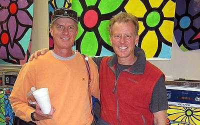 Bernie (left) and Ed Massey, co-founders of Portraits of Hope, in a laundromat with machines laminated in art by Portraits of Hope. (Laura Paresky Gould)