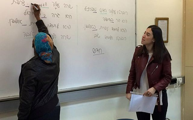 Volunteer teacher, Holon Institute of Technology student Julia Aharon (right) watches as one of her students, a cleaner at Wolfson Medical Center, writes on the board during ERETZ Hebrew class, January 2017. (Renee Ghert-Zand/TOI)