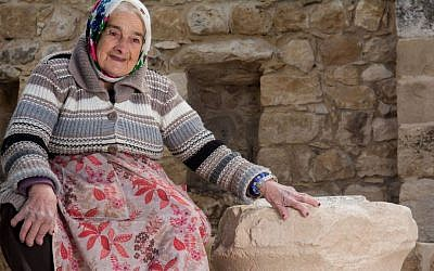Margalit Zinati, sole Jewish resident of the Druze village of Peki'in in the Galilee, with an 1,800-year-old limestone capital bearing two Hebrew inscriptions found there in February 2017. (Ritvo courtesy of Beit Zinati)