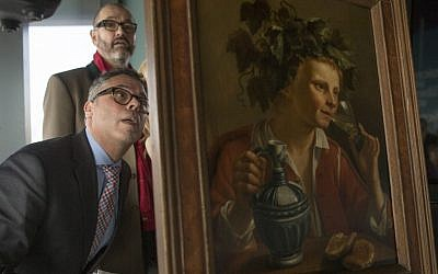 "Dr. Clarence Epstein, foreground, director of the Max Stern Art Restitution Project, inspects the back of ""Young Man As Bacchus"" by Jan Franse Verzijl during a ceremony to formally return the painting to representatives of the Max and Iris Stern Foundation, at the Museum of Jewish Heritage in New York, February 8, 2017. (AP/Mary Altaffer)"