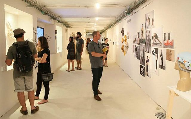 Visitors viewing artwork at the Bezalel Academy of Art and Design's annual student exhibition in Jerusalem, July 2016. (Courtesy Bezalel via JTA)