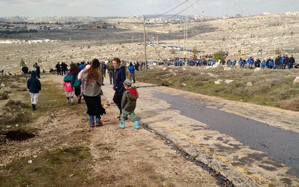 Amona parents sending their kids down the hill ahead of the evacuation, February 1, 2017 (Judah Ari Gross/Times of Israel)