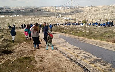 Amona parents sending their kids down the hill ahead of the evacuation, February 1, 2017 (Judah Ari Gross/Times of Israel)